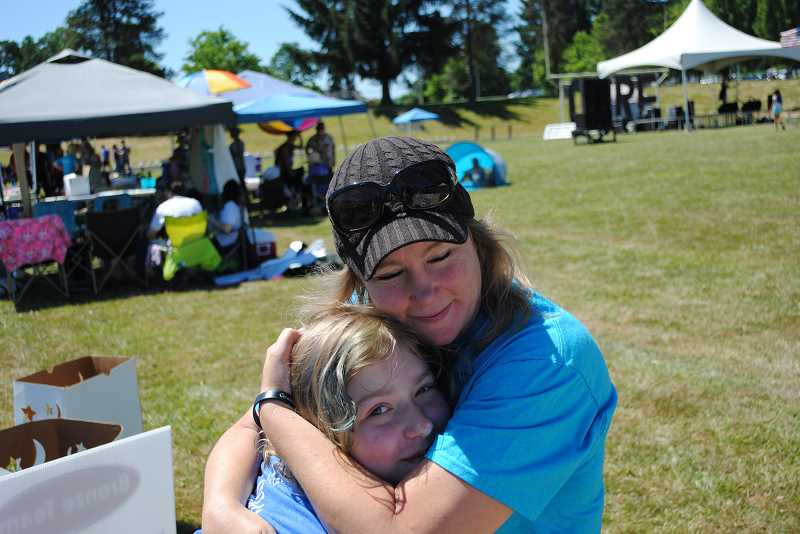NEWS-TIMES PHOTOS: EMILY GOODYKOONTZ - Tara Bohren hugs her 12-year-old daughter, Sahalie, who has been marching in the relay since she was 2, when her brother was diagnosed with cancer. Her brother died of the disease in his mid-20s. Her father also died of cancer, within two months of his diagnosis.