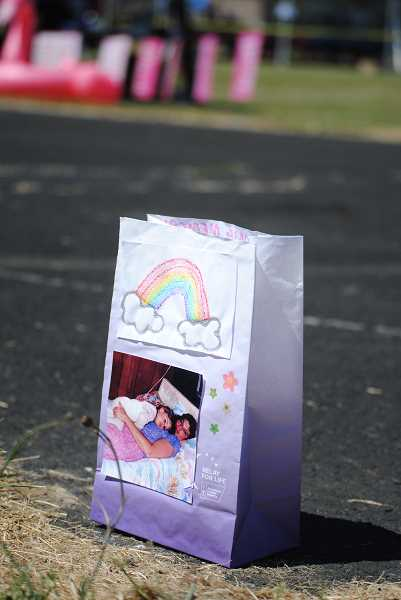 Carefully decorated luminaries make cancer issue personal.