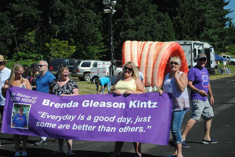 Friends and supporters carry a banner for Brenda Gleason Kintz, a previous 'Spirit of the Relay' award winner.