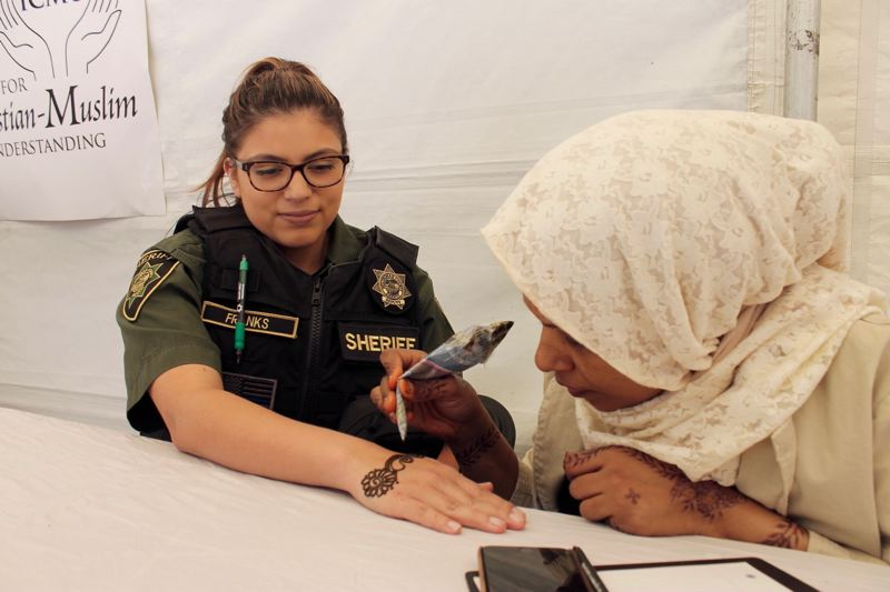 TRIBUNE PHOTO: LYNDSEY HEWITT - Zahra Habid, originally from Somalia, gives Multnomah County Sheriff's Office Corrections Deputy Sandra Franks a henna tattoo.