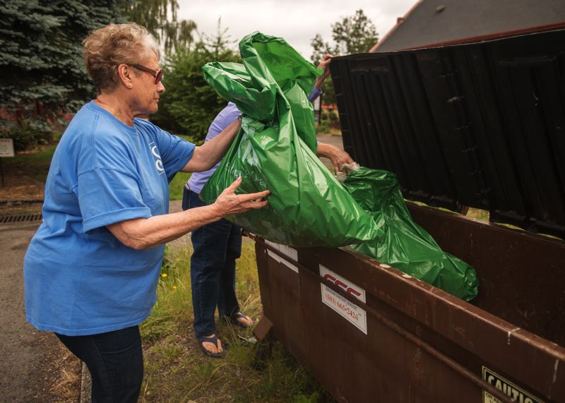 OUTLOOK PHOTO: JOSH KULLA - Nielsen estimated the women fill each garbage bag about three times during their two-mile walk around the downtown streets.