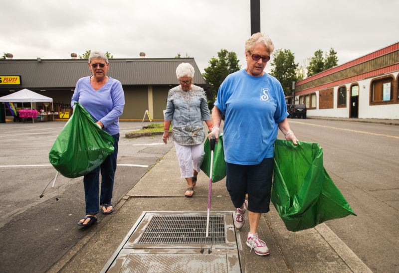 OUTLOOK PHOTO: JOSH KULLA - The city of Gresham supplied Radke, left, Douglas and Nielsen with grabbing tools and large bags to make their work easier.