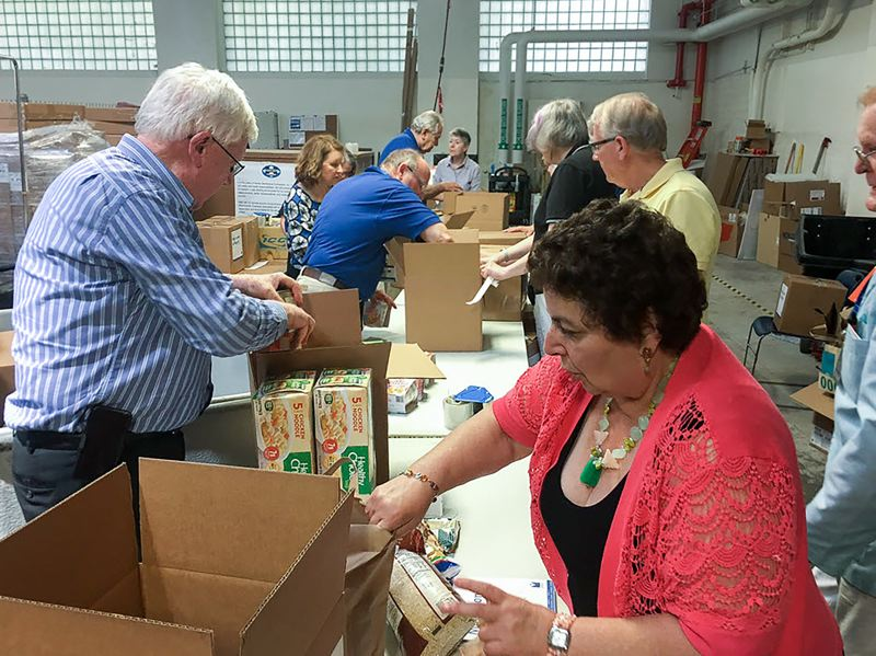 "CONTRIBUTED PHOTO - Legacy Health employees and volunteers pack some of the 21,000 pounds of food collected in the third annual ""May no one go hungry"" drive."