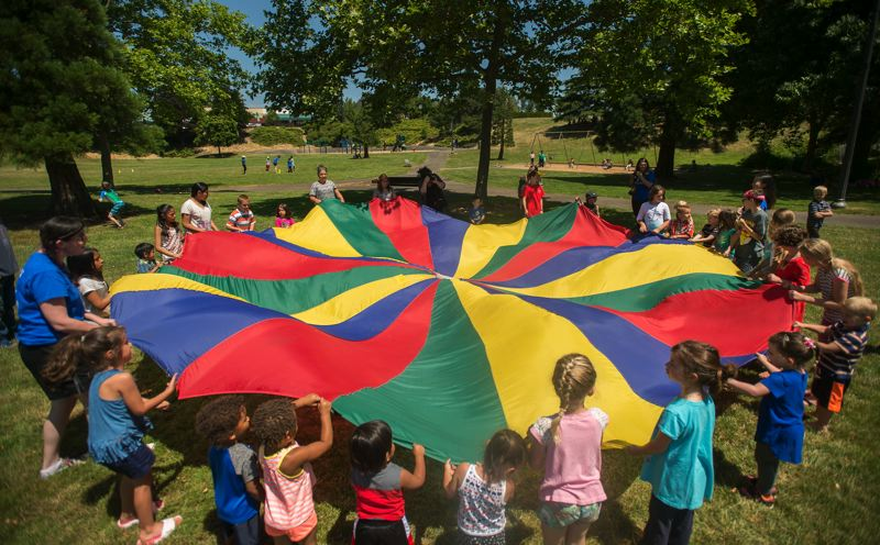 OUTLOOK PHOTO: JOSH KULLA - Kids at the city of Gresham's Summer Kids in the Park program enjoy a colorful parachute Friday at Main City Park at a celebration of the opening of the summer-long program.