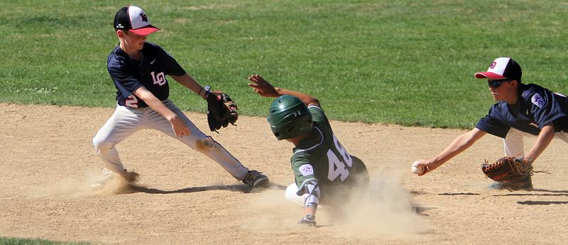 REVIEW PHOTO: MILES VANCE - Lake Oswego shortstop Charlie Grimm (left) and second baseman Brodie Heher try to tag out Tigard's Matthew Beckett during their team's 12-9 loss in the District 4 tournament at Alpenrose Dairy on Sunday.