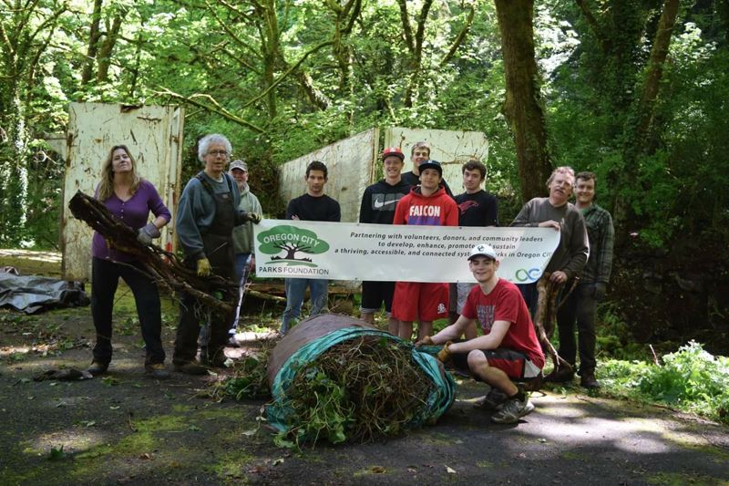 SUBMITTED PHOTO - More than 30 people attended a recent work party at Waterboard Park in Oregon City hosted by SOLVE and the Oregon City Parks Foundation. Holding the foundation's banner are board members Roger Fowler-Thias, vice president, left, and Mike Mitchell, president, far right.