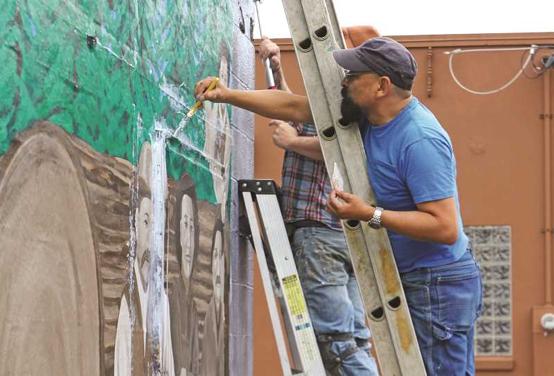 INDEPENDENT PHOTO: JULIA COMNES - Lead artist Hector H. Hernandez applies glue to the mural, which was painted on a non-woven fabric and attached to the wall in pieces, on July 7. While the mural may look done, there is still touch-up work needed before the July 27 ribbon-cutting, Hernandez said.