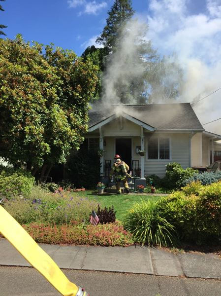 COLUMBIA RIVER FIRE AND RESCUE PHOTO - A firefighter approaches a home in St. Helens with extensive smoke coming from inside. Fire investigators say a cigarette may have caused the fire.