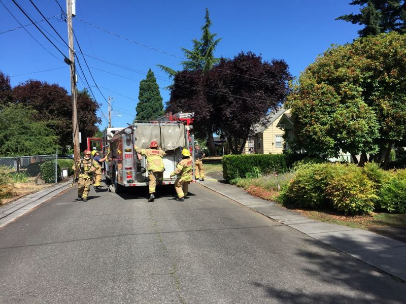 COLUMBIA RIVER FIRE AND RESCUE PHOTO - Firefighters with Columbia River Fire and Rescue approach the scene of a house fire in St. Helens Tuesday morning.  The fire spread to the attic and crews had to cut holes in the roof to vent heavy smoke and heat.