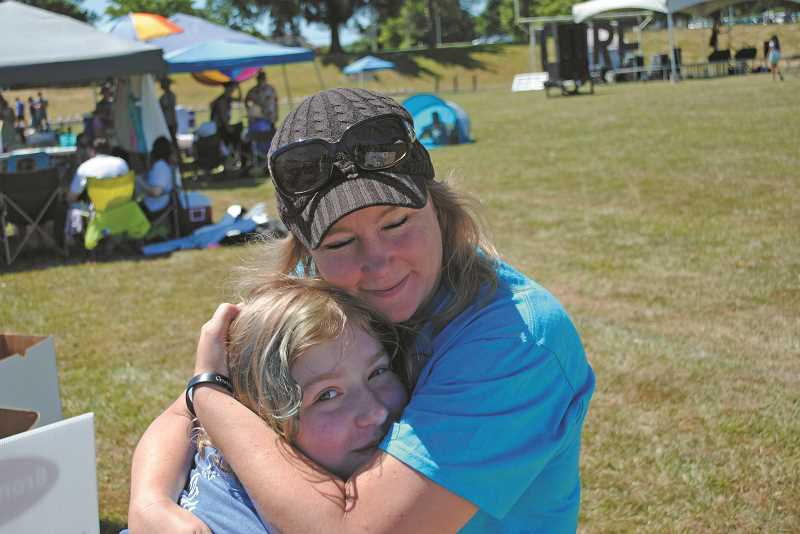 NEWS-TIMES PHOTOS: EMILY GOODYKOONTZ - Team Captain Tara Bohren of team Will Walk for Cure hugs her daughter Sahalie, captain of Bohren Strong, at the Relay For Life of Western Washington County. Bohren lost her brother to cancer and Sahalie lost her father to cancer just a few years later.