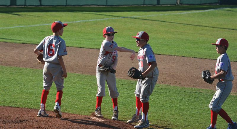 TIMES PHOTO: MATT SINGLEDECKER - Raleigh Hills infielders Noah Koopman and Ryan Hoffmann celebrate a nice defensive play against Beaverton-Aloha.