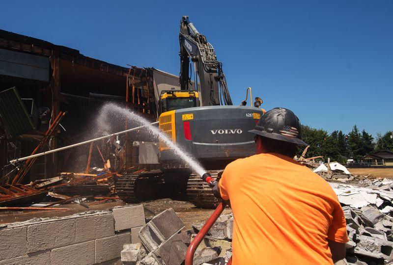 OUTLOOK PHOTO: JOSH KULLA  - The demolition work at Troutdale Elementary School is sprayed with a jet of water to keep the dust from fouling the air and nearby neighborhoods.