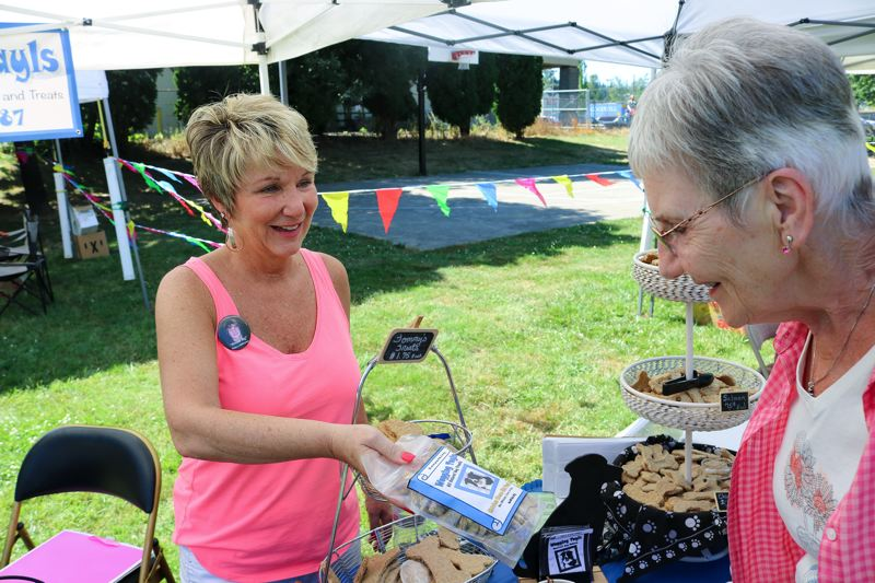 OUTLOOK PHOTO: ZANE SPARLING - Wagging Tayls owner Darla Sturdy hands a customer a bag of doggy treats during the Damascus Farmers Market on Thursday, June 6.