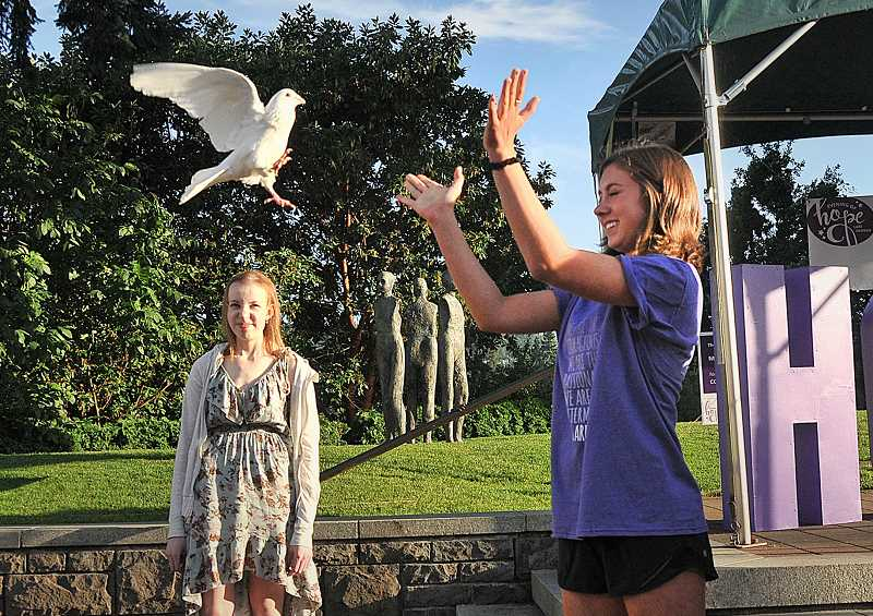 REVIEW PHOTO: VERN UYETAKE - West Linn High School senior Liz Lofurno was the first to release a dove Friday evening as a symbol of hope after sharing her story of battling cancer.
