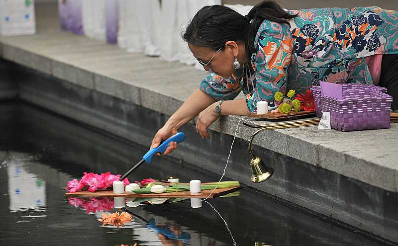 REVIEW PHOTO: VERN UYETAKE - Volunteer Susan Dassise lights candles on one of the floating platforms that filled the reflecting pool Friday at the Evening of Hope in Millennium Plaza Park.