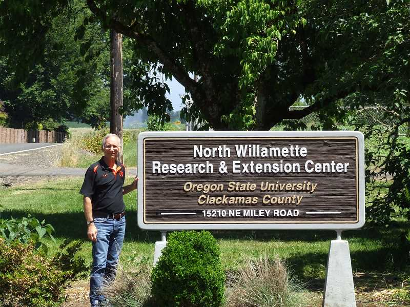 SUBMITTED PHOTO - Lake Oswegan Mike Bondi, the director at the North Willamette Research and Extension Center, poses at the entry sign to the center, located south of Wilsonville. He invites all to attend the centers free open house event July 19.