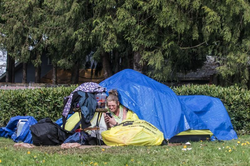 TRIBUNE PHOTO: JONATHAN HOUSE - A homeless woman camps near the back fences of homes in the Lents neighborhood in Southeast Portland.