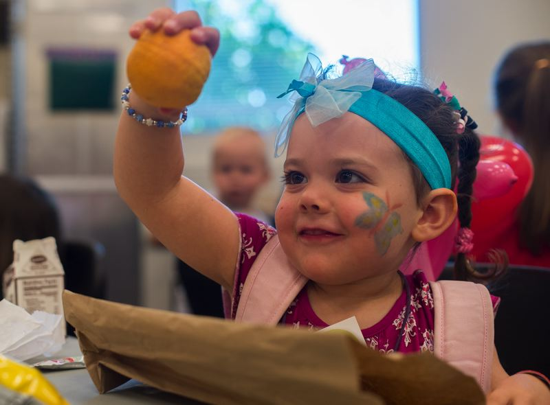 OUTLOOK PHOTO: JOSH KULLA - Greta Gordon, 4, of Gresham, enjoys an orange with lunch Wednesday at the kickoff of the Gresham Library's summer lunch program. The program offers free lunches to kids under 18 on weekdays through Aug. 25.
