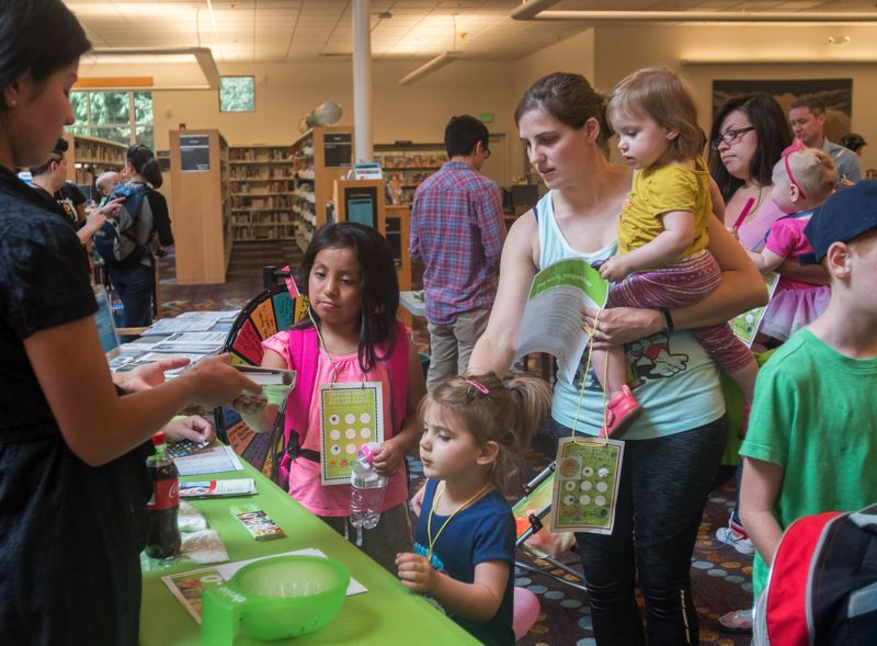 OUTLOOK PHOTO: JOSH KULLA - Jamie Daily and her daughters, Layla, 3, and Winnie, 18 months, enjoy game day at the Gresham Library Wednesday as part of the start of the library's summer lunch program for children.