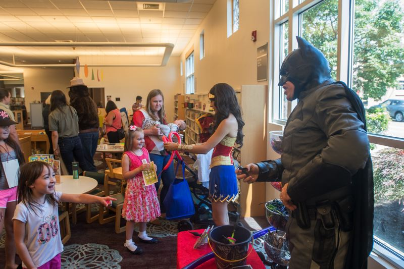 OUTLOOK PHOTO: JOSH KULLA - Batman and Wonder Woman create balloon animals for kids Wednesday at the Gresham Library's game day.