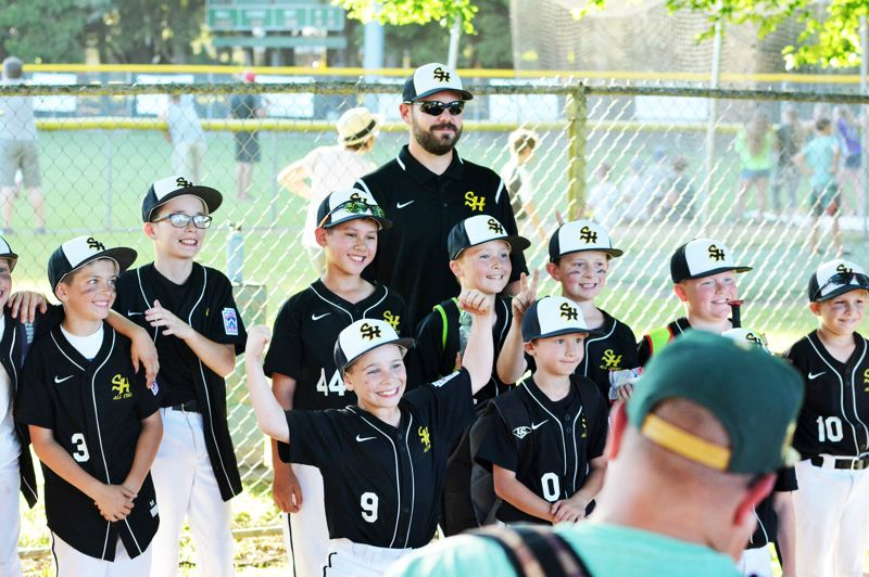 SPOTLIGHT PHOTO: JAKE MCNEAL - Cody Bartlett (9), Johnny Butler (3), Carson McKenzie (44), Carter Nelson (0), Zack Liebelt (10) and St. Helens' 8-to-10-year-old Minors celebrate their seven-inning 15-14 District 1 Tournament second-round consolation walk-off and sweep of Scappoose on Friday, July 14, at Erv Lind Field in Portland.