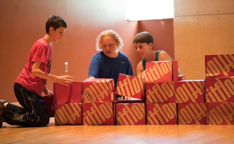 TIMES PHOTO: JAIME VALDEZ - From left to right, 13-year-old Tigard Library patrons Cody Bonn, Eli Webster and Kyler Bonwell stack cardboard boxes to form a wall they think will be difficult to knock down with a trebuchet.