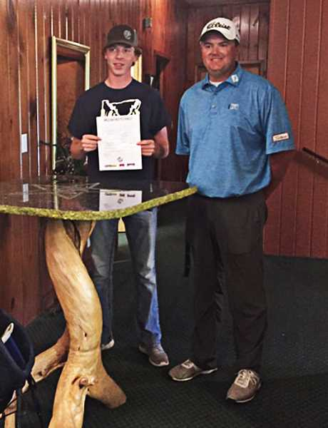PHOTO COURTESY OF CROOK COUNTY HIGH SCHOOL GOLF - Mayson Tibbs, left, holds up his letter of intent as he stands with CCHS head boys golf coach Zach Lampert during the golf awards banquet late this spring.