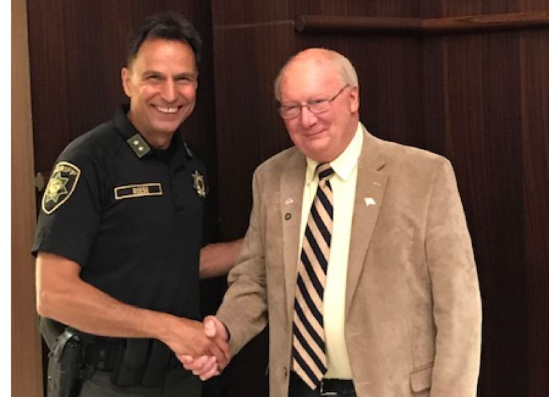 COURTESY PHOTO - Sheriff Mike Reese shakes hands with Fairview Mayor Ted Tosterud.