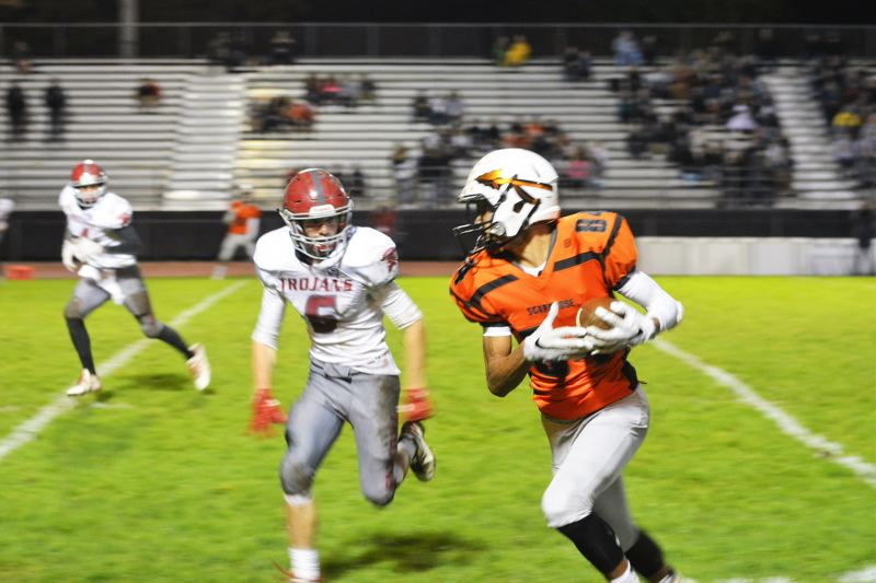 SPOTLIGHT PHOTO: JAKE MCNEAL - Indians senior wide receiver Tevin Jeannis turns upfield in Scappoose's Class 4A play-in round win over Douglas last fall.
