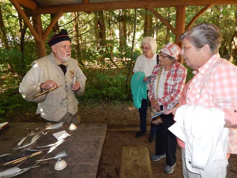 A guide on the grounds of the Fort Clatsop replica, dressed in authentic garb, shows members of the King City Travel Club quills like the explorers would have used for writing in their journals.