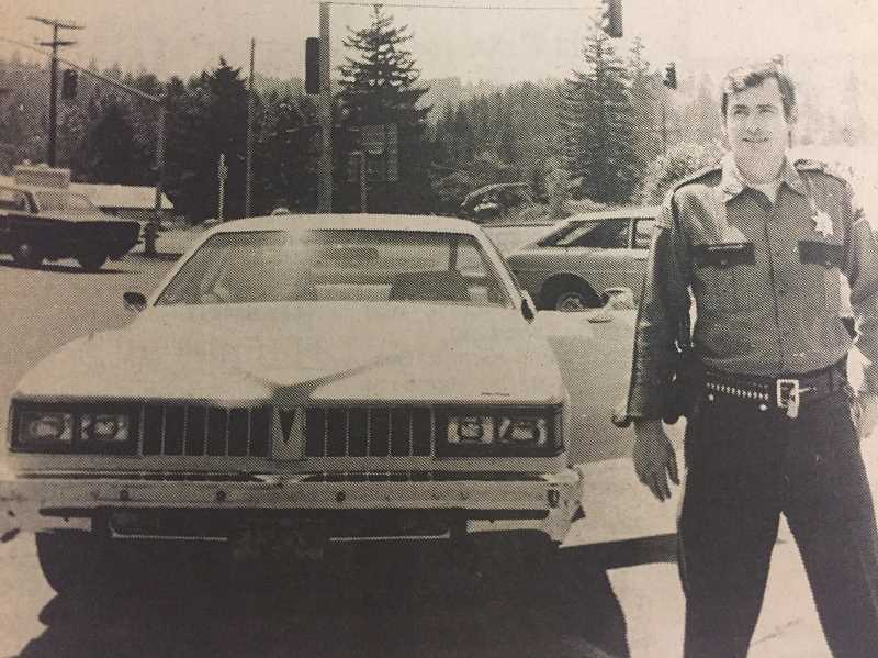 ARCHIVE PHOTO - Patrol officer Rick Walsh stands next to the Estacada Police Dpeartments new vehicle in 1977. Previously, the department had been down to one car.