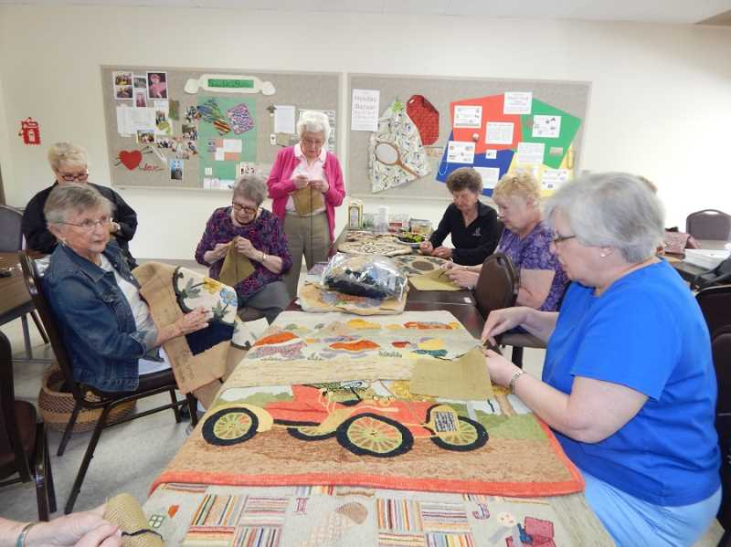 REGAL COURIER PHOTO: BARBARA SHERMAN - Members of the Summerfield Craft Club try their hand at rug hooking at their June meeting; on the table are some examples of rug-hooking brought in by a guest.