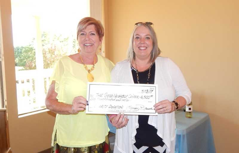 REGAL COURIER PHOTO: BARBARA SHERMAN - Sandy Brewer (left), chair of the Summerfield Women's Golf Club's charity fundraiser, turns over a check for $6,500 to Renee Brouse, new director at the Good Neighbor Center.