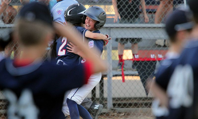 REVIEW PHOTO: MILES VANCE - Lake Oswego's Finley Smith (center, no. 2) hugs teammate Matt Layne after Layne's hit in the seventh inning drove home Smith with the winning run in their team's 8-7 victory over Bend North at Holland Youth Park in Salem on Tuesday.