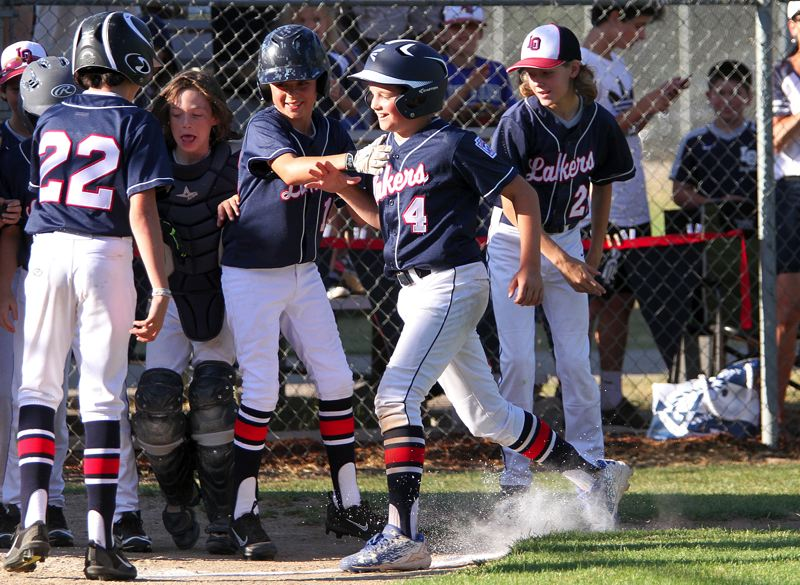 REVIEW PHOTO: MILES VANCE - Lake Oswego's Ryan Oliver (no. 4) is greeted at home after hitting a home run in his team's 8-7 win in seven innings over North Bend at the Oregon 9/11 state tournament at Holland Youth Park in Salem on Tuesday.