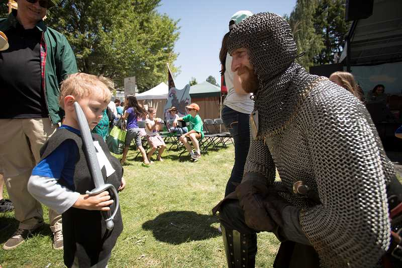 PAMPLIN MEDIA GROUP: JAIME VALDEZ - William Edman,4, of Woodbridge, California, shows his skills to Jordin Mitchell, an actor with the Seattle Knights  during the 2017 Robin Hood Festival. Photo by Jaime Valdez