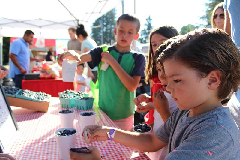 TIDINGS PHOTO: SAM STITES - Carter Sue collects his tokens to pay for blueberries from Schotts Blueberry Farm at the West Linn Summer Market. Sue is a member of the Power of Produce club which gives him $2 each week to spend on local produce.