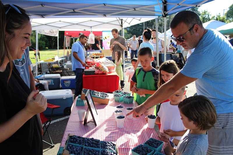 Emily Christensen (left) of Schotts Blueberry Farm watches as Jaron Sue (right) helps his children Carter, Mason and Jane pick out blueberries using the tokens they received through the Power of Produce program at the West Linn Summer Market.