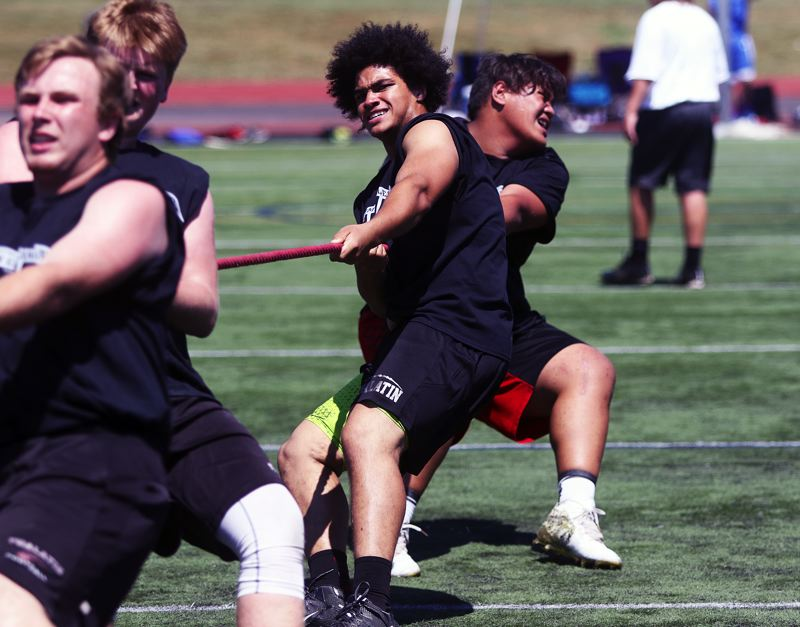 DAN BROOD - Tualatin linemen, including Gerald Saina (right) and Jarius Jackson, strain during the tug-of-war competition at the Metro Area Lineman Challenge.
