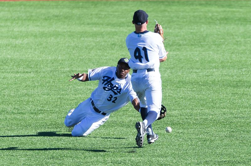 HILLSBORO TRIBUNE PHOTO: CHRISTOPHER OERTELL - Hillsboro Hops centerfielder Tramayne Holmes (32) called off shortstop Camden Duzenack (41) from a pop fly but missed catching the ball during a minor league baseball game against the Spokane Indians at Ron Tonkin Field in Hillsboro, Oregon.