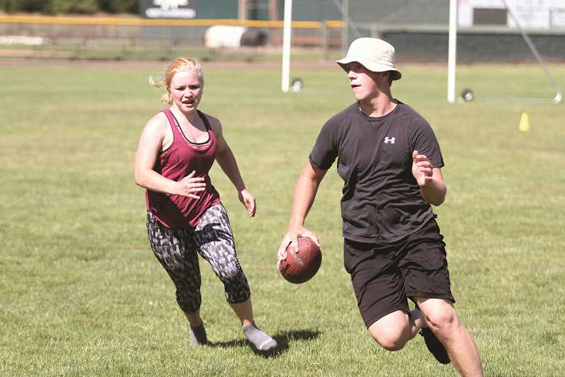 PHIL HAWKINS - North Marion senior Rose Rostocil chases down sophomore Dylan Delpha during a cooldown football game at Husky Boot Camp.