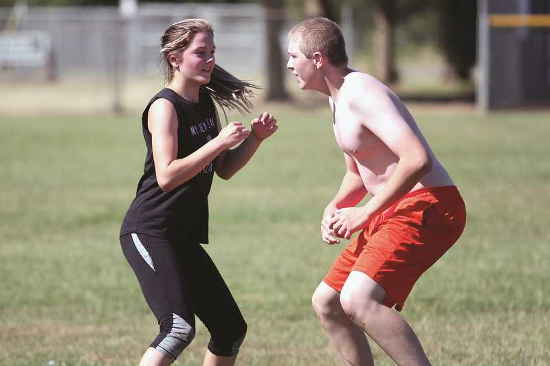 PHIL HAWKINS - North Marion senior Taylor Bundy defends junior William Bishop during a cooldown game of football at the Husky Boot Camp last week. Bundy and senior cheer teammate Rose Rostocil took part in the annual July fitness camp to help condition for the coming cheer season.