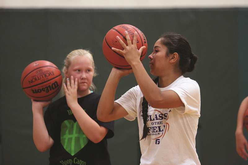 PHIL HAWKINS - North Marion junior guard Mar Verastegui (right) volunteered to assist high school girls basketball head coach Trevor Bodine during the Huskies' summer girls basketball camp last week.