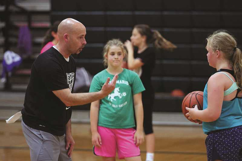 PHIL HAWKINS - North Marion High School girls basketball coach Trevor Bodine helps lead a pair of girls through a drill at his summer basketball camp last week.