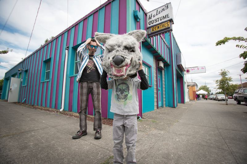 TRIBUNE PHOTO: JAIME VALDEZ - Warner Clark, 5, tries on a wolf head provided by Helen's Pacific Costumers employee Jay Lieber, left. The 127-year-old business in Northeast Portland has been forced to ditch the storefront format. Lieber has been working to start a nonprofit and save the costumes. Find out more: helenspacificcostumers.com/save-the-costumes.