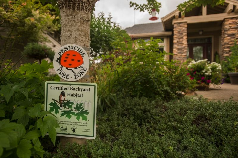 OUTLOOK PHOTO: JOSH KULLA - Susan Spencer displays her Backyard Habitat Certification sign in front of her home.