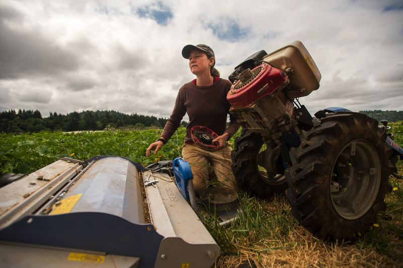 OUTLOOK PHOTO: JOSH KULLA - Emily Cooper, owner of Full Cellar Farms, tends to a rototiller during a recent workday at her plot at the Headwater Farms incubator farm in east Gresham.
