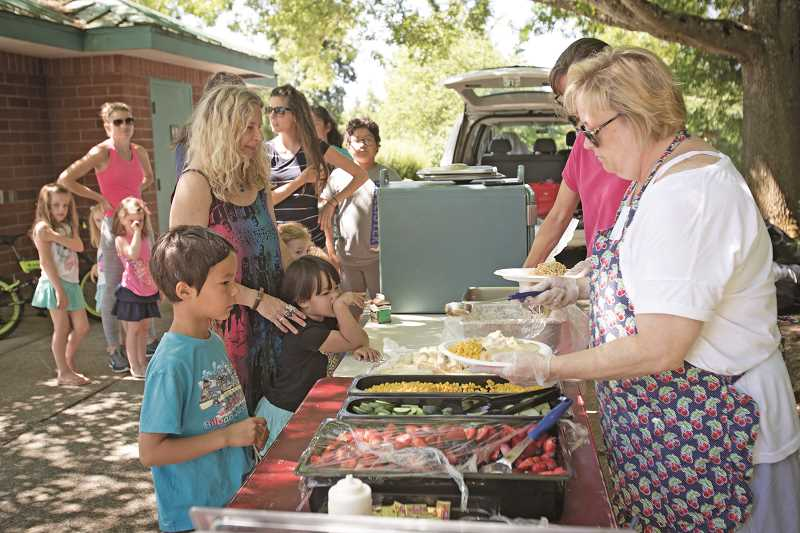 JAIME VALDEZ - Families line-up for free lunches provided by Tigard-Tualatin School District at Atfalati Park.