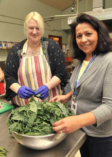 REVIEW PHOTO: VERN UYETAKE - Adult Community Center Chef Sara Schrader (left) and Administrative Assistant Pam Montoya prepare a salad using fresh greens from their new Cook's Garden.