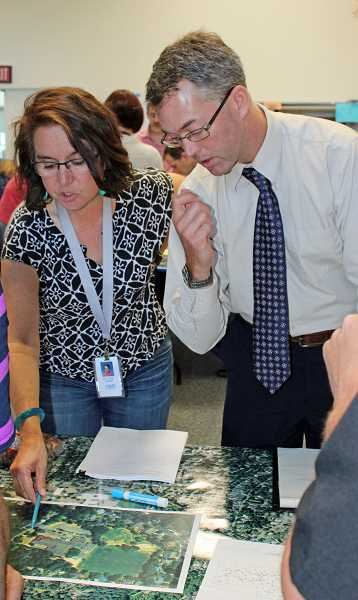 REVIEW FILE PHOTO: JILLIAN DALEY - Oak Creek Elementary Principal Lilian Sarlos (left) and Lake Oswego High School Assistant Principal Ryan Rosenau run through a disaster response during an emergency training exercise in August 2016.